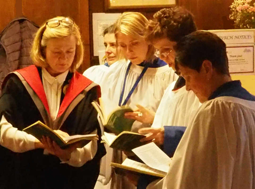 Verger, Penny Waters (left), running through some final points with choir members.