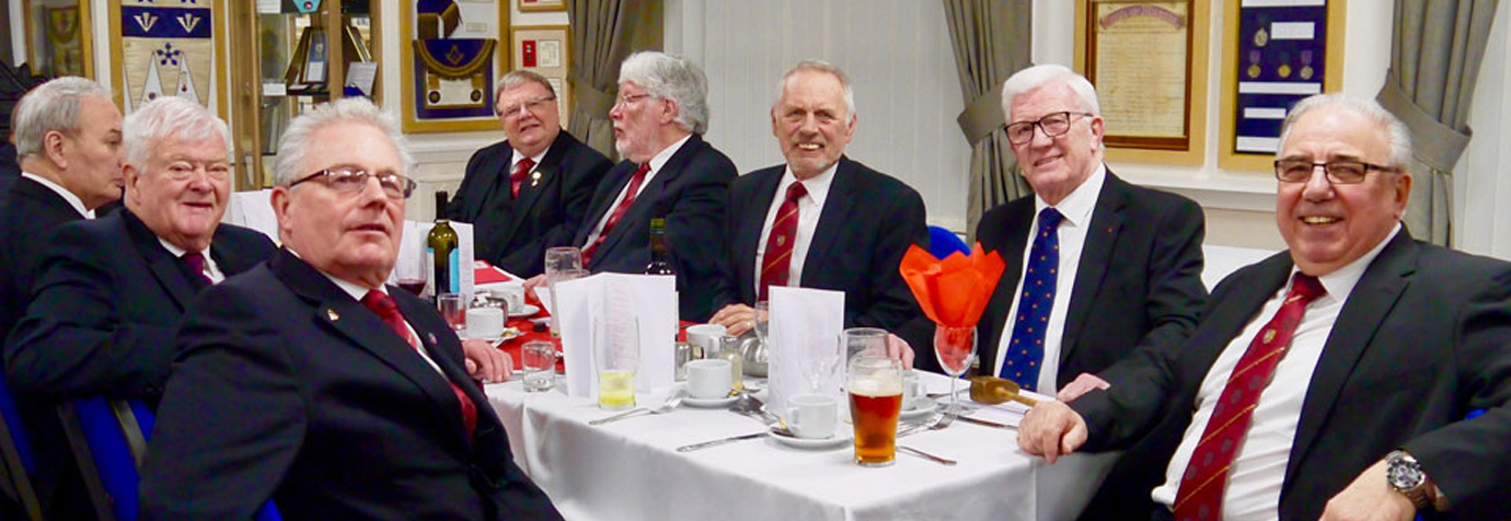 Companions enjoying the festive board with some museum exhibits in the background.