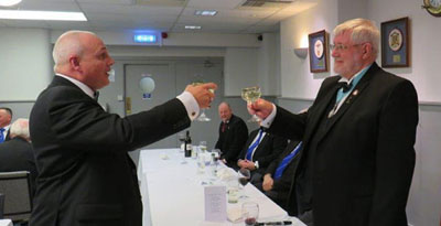 John Darrell (left) toasting Brian Crawford during the master's song.
