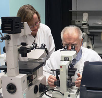 Derek examines cells under the microscope closely watched by Dr Helen Wright