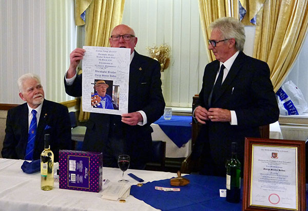 Pictured from left to right, are: David Randerson, George Holden (with a poster signed by the guests) and Richard Olley.