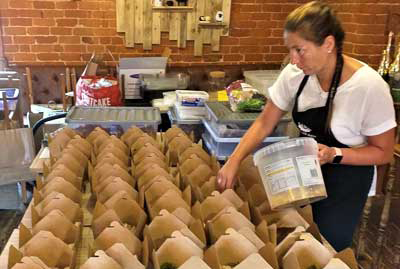 Tearoom manager checking the afternoon tea boxes before dispatch