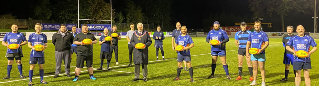Paul Renton (centre) presenting the rugby balls to the Typhoons players.