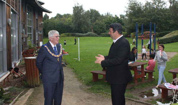Dave McNicholl (right) of Warrington Youth Centre explaining the facilities to Tony as children enjoy the play area.