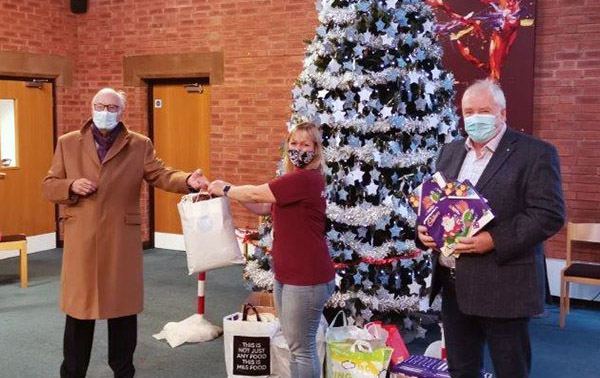 Peter Greathead (left) presenting gifts and selection boxes to Michelle Lonican, with Alan Berwick.