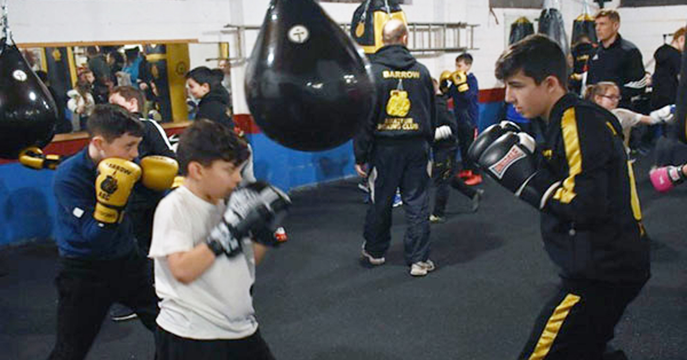 Ethan Holt of Barrow ABC (right) helping coach the next generation of young boxers.