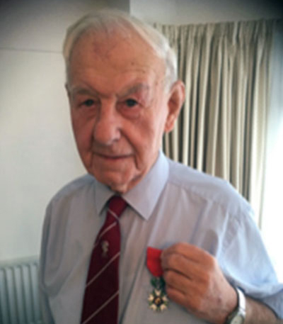 Les Chadwick proudly displays his medal.