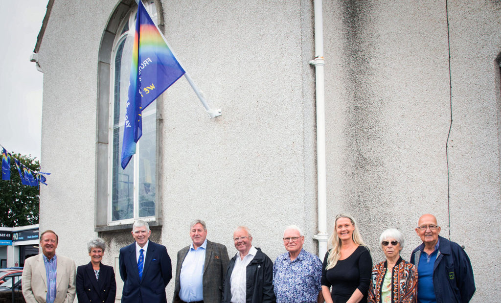 Provincial Grand Master Tony Harrison (third from the left) and his wife Maureen, together with members of the Lancaster group under the flag at Rowley Court.