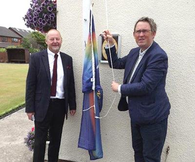 John Cross (left) and Paul Maynard MP raising the flag